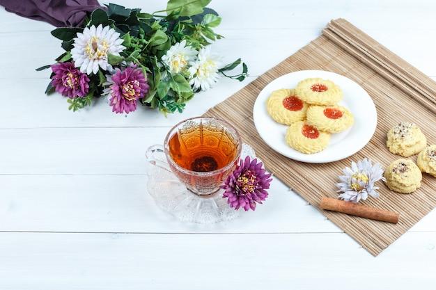 Biscoitos, canela em um jogo americano com flores, xícara de chá, vista de alto ângulo em um fundo branco de placa de madeira