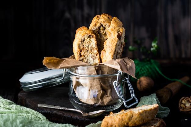 Biscoitos cantuccini italianos em uma jarra de vidro com fundo escuro elegante