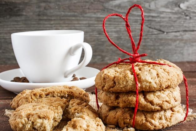 Biscoitos caseiros, amarrados com fita vermelha em forma de coração com café c