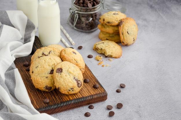 Biscoitos caseiros americanos tradicionais com pedaços de chocolate em uma prancha de madeira velha sobre uma superfície cinza com garrafas de leite e palha. orientação horizontal. copie o espaço