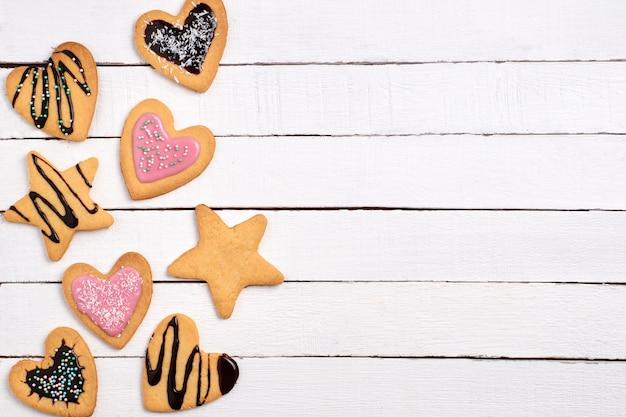 Biscoitos caseiros, biscoitos encaracolados com glacê rosa e chocolate.