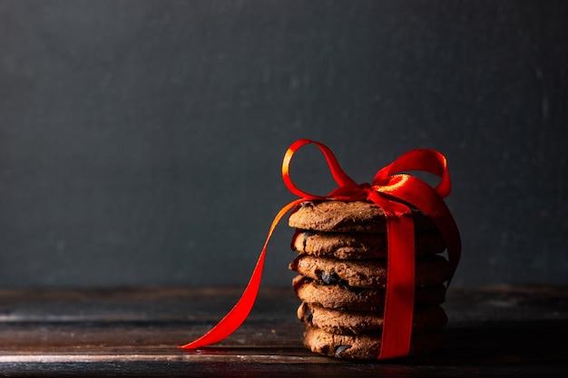 Biscoitos caseiros com gotas de chocolate amarrados com uma fita vermelha em estilo rústico.