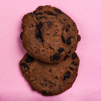 Biscoitos caseiros com gotas de chocolate em formato quadrado de fundo rosa