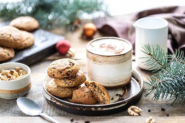 Biscoitos caseiros com nozes e café em uma xícara de cerâmica sobre uma mesa de madeira com brinquedos e galhos de árvores de natal.