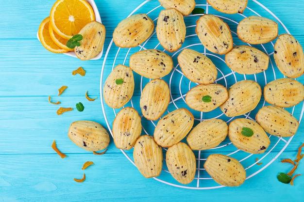 Biscoitos caseiros. cookies franceses madeleines com suco de laranja e lascas de chocolate.