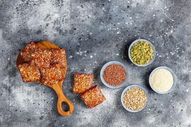 Biscoitos caseiros de estaladiço com sementes de gergelim, aveia, abóbora e girassol. lanche saudável, bolachas
