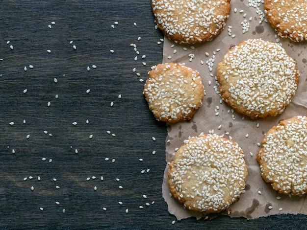 Biscoitos caseiros de tahine vegan são dispostos em uma mesa escura