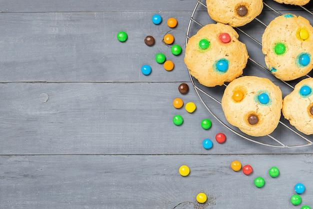 Biscoitos caseiros decorados com balas de gelatina colorida em fundo cinza