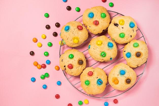 Biscoitos caseiros decorados com balas de gelatina colorida em fundo rosa