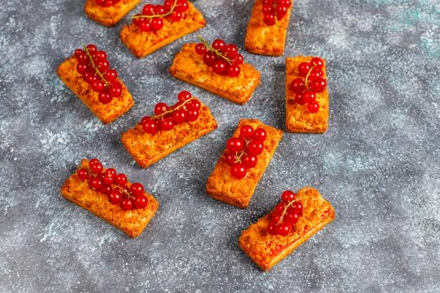 Biscoitos caseiros deliciosos do atolamento de groselha com bagas frescas.