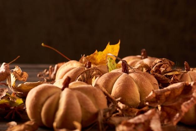 Biscoitos caseiros em forma de abóbora em folhas de outono. biscoitos artesanais de halloween em uma tabela, close-up