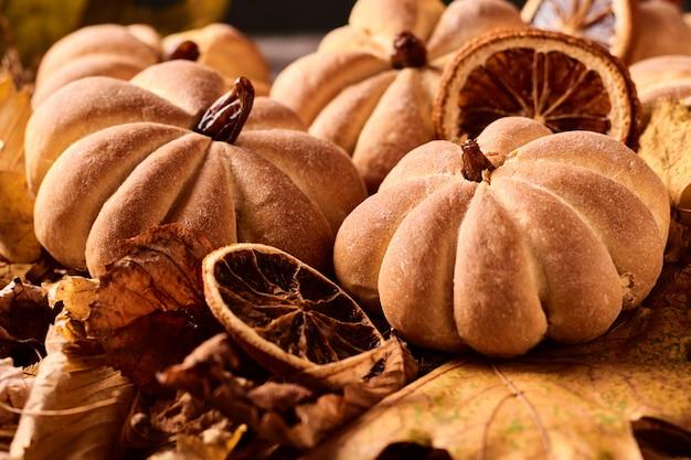 Biscoitos caseiros em forma de abóbora no outono folhas. biscoitos artesanais de halloween em uma mesa, close-up
