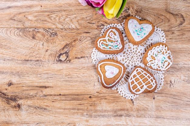 Biscoitos caseiros em forma de coração, decorados com glacê branco com granulado decorativo, mentem sobre um guardanapo de crochê sobre uma mesa de madeira, vista superior com espaço para texto.