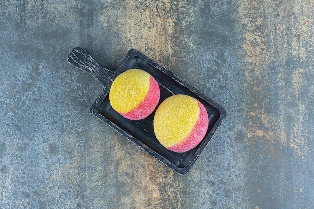 Biscoitos caseiros em forma de pêssego doce na placa de madeira, na superfície de mármore.