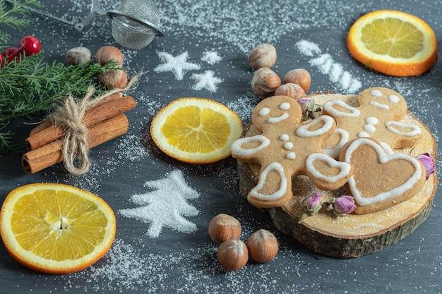 Biscoitos caseiros na placa de madeira com várias decorações. nozes, neve e rodelas de laranja.