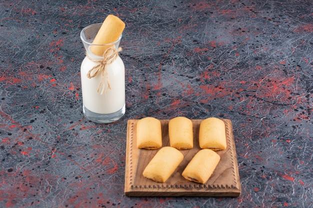Biscoitos caseiros na placa de madeira e garrafa de leite no rústico.