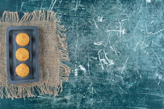 Biscoitos caseiros num prato de madeira na toalha, na mesa azul.