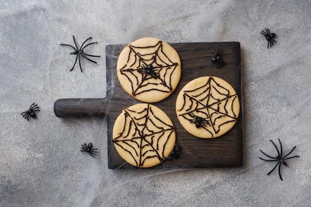 Biscoitos caseiros para o halloween, cookies com teia de chocolate e aranhas