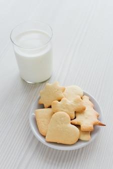 Biscoitos caseiros recém-assados e um copo de leite na madeira branca
