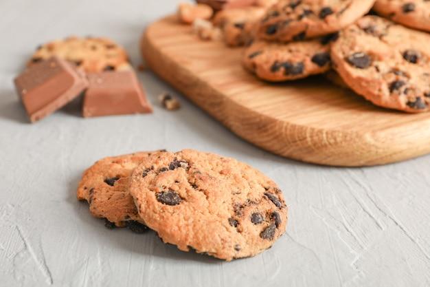 Biscoitos caseiros saborosos dos pedaços de chocolate no fundo cinzento