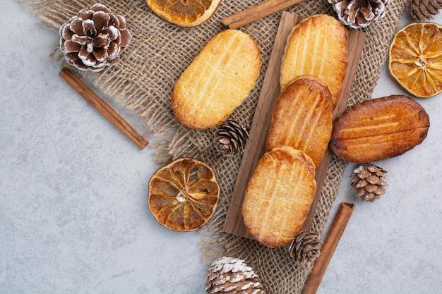 Biscoitos caseiros sobre serapilheira com pinhas e frutos secos. foto de alta qualidade