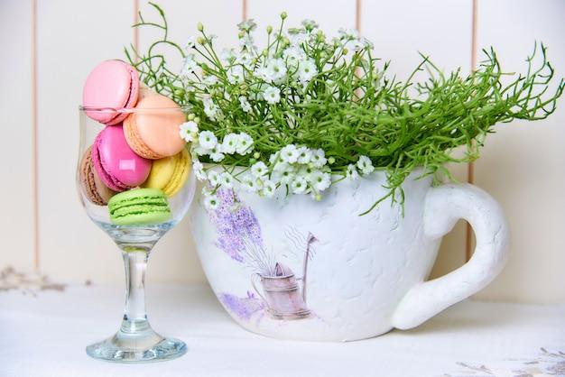Biscoitos coloridos brilhantes em um vidro perto de um vaso decorativo bonito com flores.