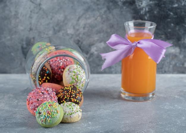 Biscoitos coloridos com granulado em frasco de vidro e suco de laranja.
