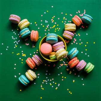 Biscoitos coloridos de macaron em um fundo verde em uma xícara