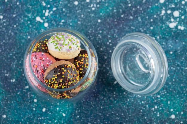 Biscoitos coloridos decorados com granulado em frasco de vidro.