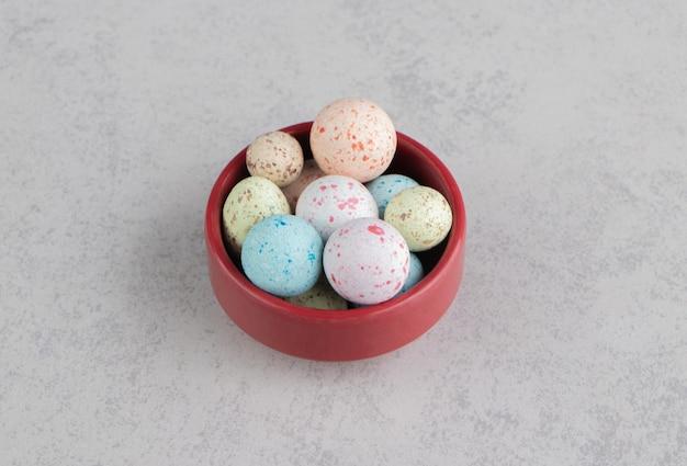 Biscoitos coloridos no prato, na superfície do mármore