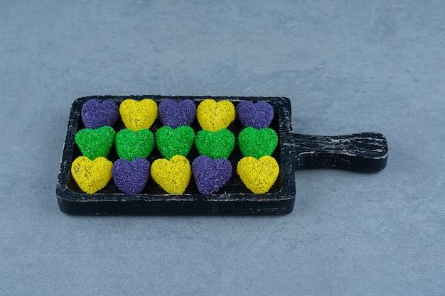 Biscoitos coloridos no quadro, na mesa de mármore.
