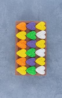 Biscoitos coloridos no quadro, no fundo de mármore.