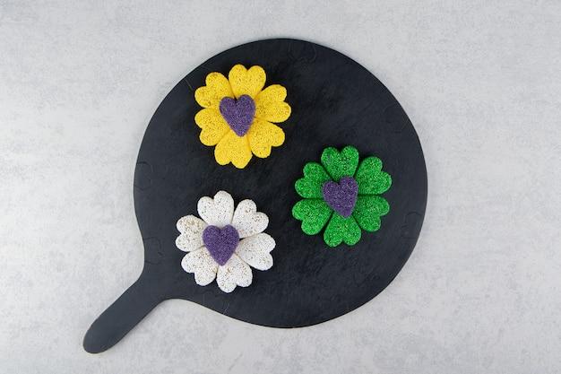 Biscoitos coloridos no tabuleiro na superfície do mármore