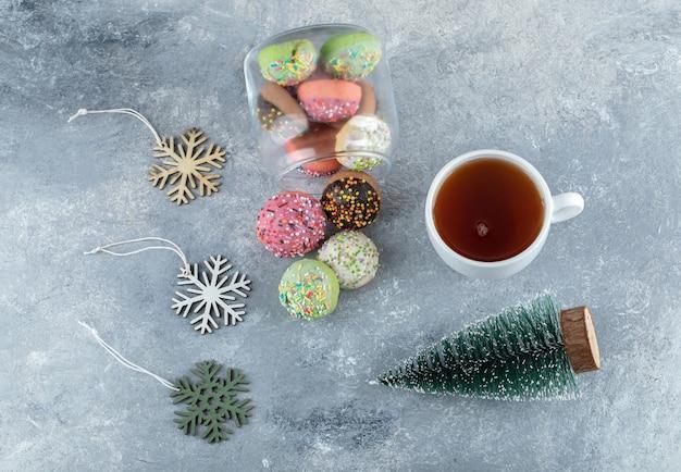 Biscoitos coloridos, pinheiro e chá na mesa de mármore.