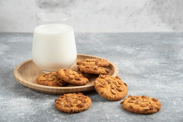 Biscoitos com amendoim orgânico e copo de leite na placa de madeira.