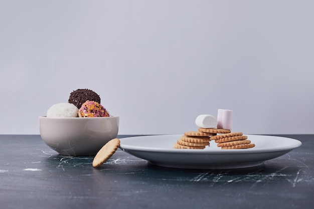 Biscoitos com biscoitos de marshmallow em pratos brancos no azul.
