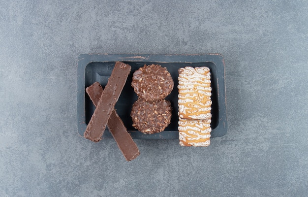 Biscoitos com biscoitos redondos de chocolate em um quadro escuro