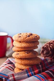 Biscoitos com caneca vermelha de chocolate quente, cone na mesa de madeira