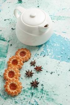 Biscoitos com chaleira na superfície azul-clara de vista de cima
