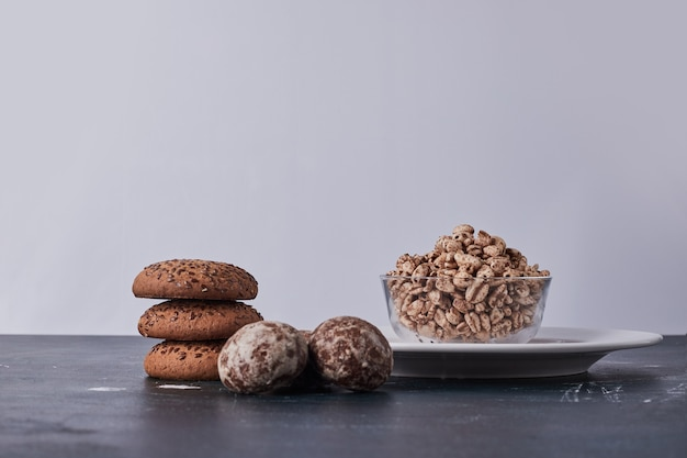 Biscoitos com cominho, aveia e pão de gengibre com pipoca de trigo ao redor.
