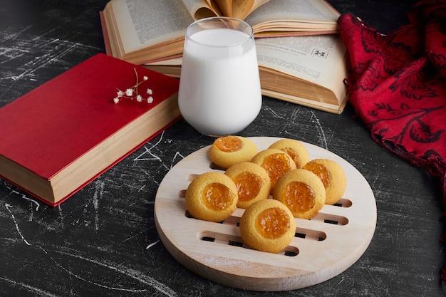 Biscoitos com compota de citrinos e um copo de leite.