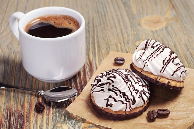 Biscoitos com creme e xícara de café na velha mesa de madeira