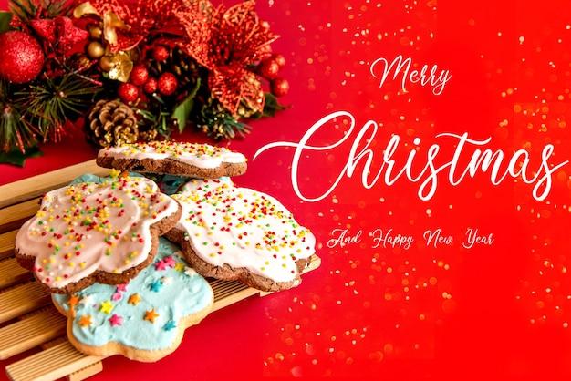 Biscoitos com decoração de natal em fundo vermelho.