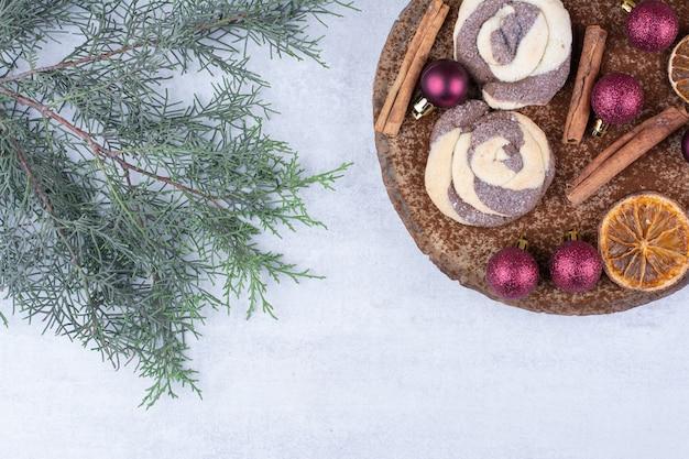 Biscoitos com enfeites, canela e rodelas de laranja na peça de madeira.