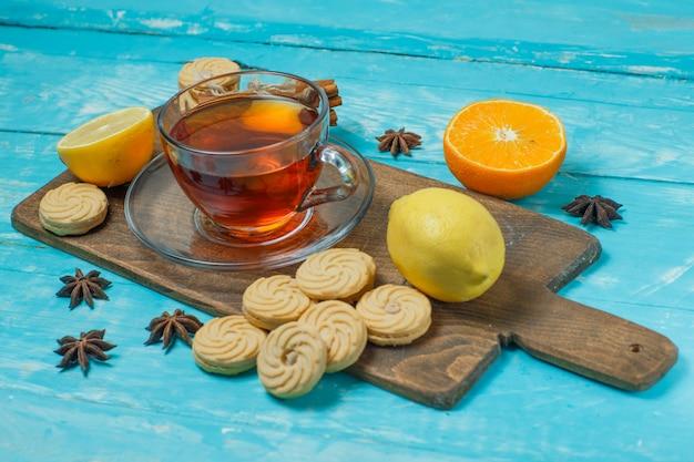 Biscoitos com especiarias, chá, limão, laranja em azul e placa de corte, vista de alto ângulo.