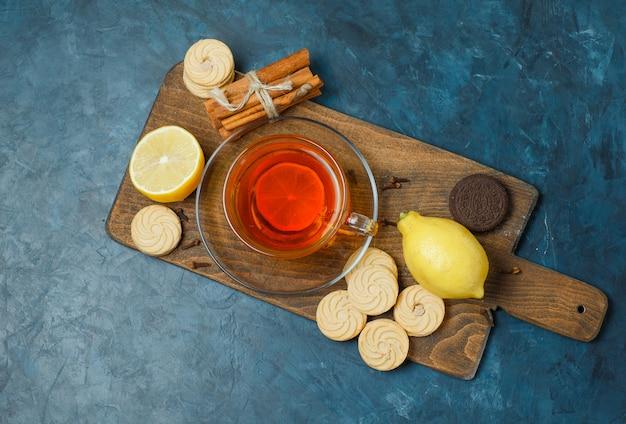 Biscoitos com especiarias, chá, limão vista de cima em azul escuro e tábua de cortar