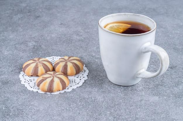 Biscoitos com estampa de zebra e xícara de chá na superfície de mármore