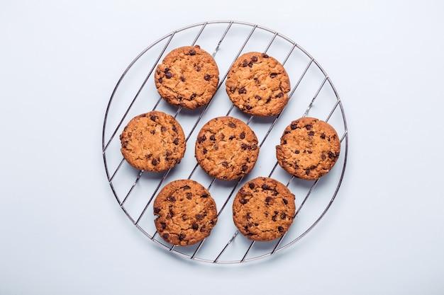 Biscoitos com gotas de chocolate de aveia em uma grelha redonda para esfriar. fundo azul minimalista