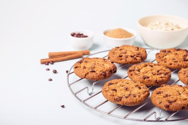Biscoitos com gotas de chocolate de aveia em uma grelha redonda para resfriamento e ingredientes