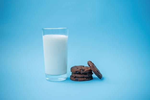 Biscoitos com gotas de chocolate em um prato sobre a mesa e um copo de leite